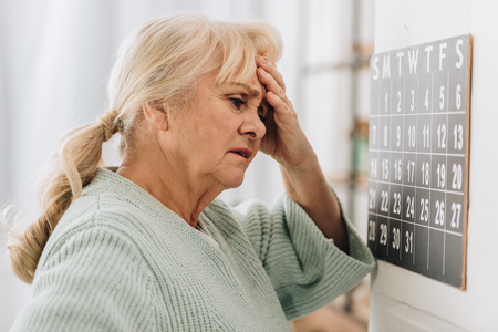 upset woman with gray hair touching head and looking at wall calendar