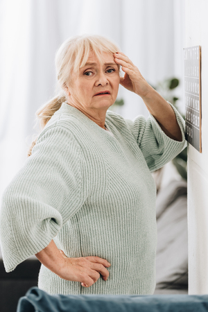 upset senior woman standing near calendar on wall and holding head Banque d'images - 117439776