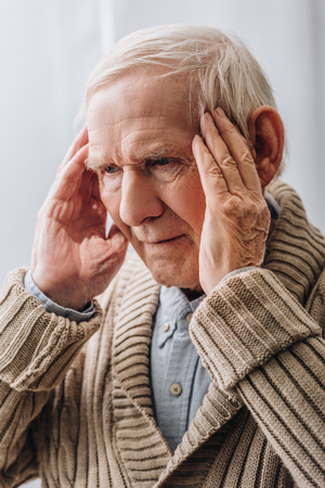 close up of pensioner with grey hair having headache at home