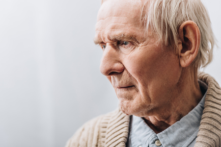 Nahaufnahme eines traurigen Rentners mit grauen Haaren zu Hause