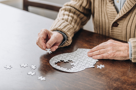 cropped view of senior man playing with puzzles 版權商用圖片