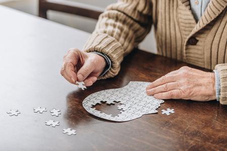 Vista recortada del hombre mayor jugando con rompecabezas Foto de archivo