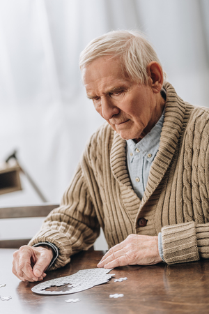 sad retired man with grey hair playing with puzzles at home Stock Photo