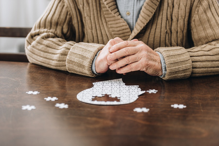cropped view of retired man playing with puzzles on table Stock Photo