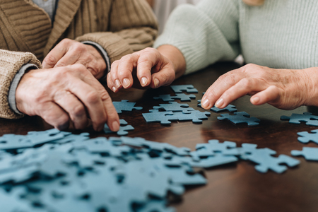 cropped view of retired couple playing with puzzles at home 免版税图像