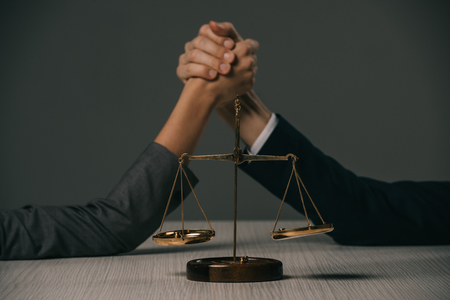 cropped view of businesspeople arm wretsling on wooden table with scales of justice on grey