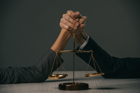 partial view of businessman and businesswoman arm wretsling on wooden table with scales of justice on grey Stock Photo