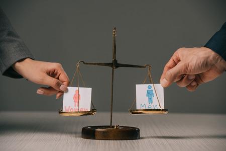 Vista recortada de empresarios con signos masculinos y femeninos en la balanza de la justicia, concepto de igualdad de género