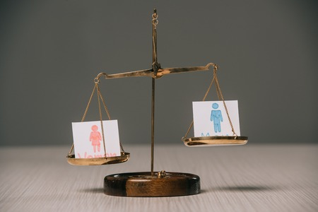 male and female signs on scales on wooden table, gender equality concept