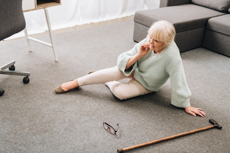 lonely senior woman with blonde hair sitting on floor in living room Banco de Imagens