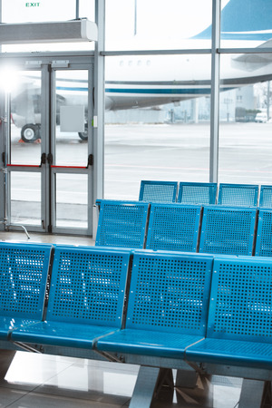 empty departure lounge with blue metallic seats in airport