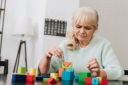 blonde retired woman playing with wooden toys at home