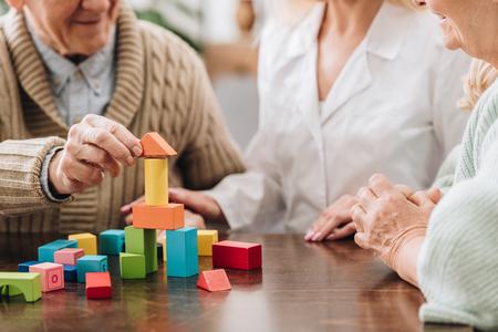 przycięty widok opiekuna siedzącego z emerytowanym mężczyzną i kobietą i bawiącego się drewnianymi zabawkami