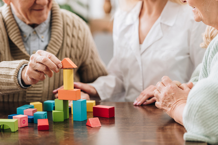 Vista recortada del cuidador sentado con un hombre y una mujer jubilados y jugando con juguetes de madera