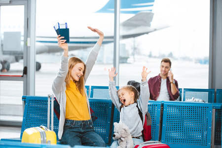 selective focus happy mother and daughter holding hands above head and smiling in airport with man on background Stock Photo