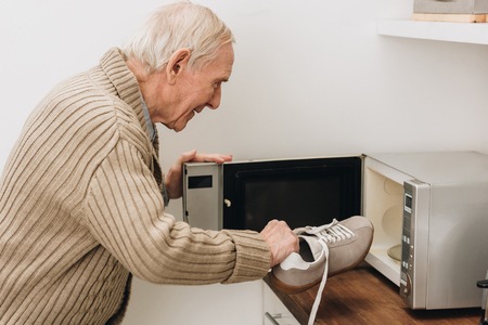 retired man with dementia disease putting shoe in microwave oven