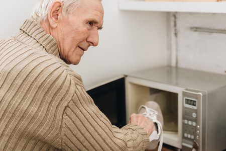 senior man with dementia disease putting shoe in microwave oven