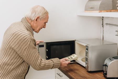 senior man with dementia disease putting dollars in microwave oven