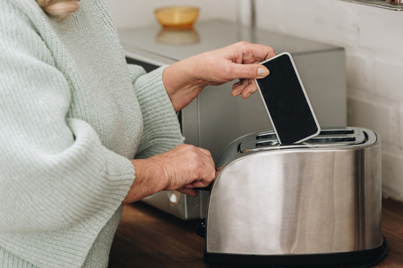 cropped view of retired woman with dementia disease putting smartphone with blank screen in toaster