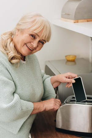 cheerful retired woman with alzheimer disease putting smartphone in toaster