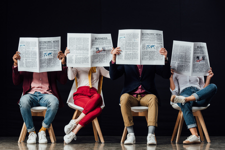 group of casual businesspeople with obscure faces sitting on chairs and reading business newspapers isolated on black