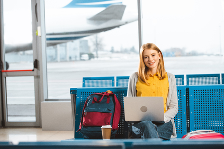 beautiful woman sitting with laptop near backpack and disposable cup in airport