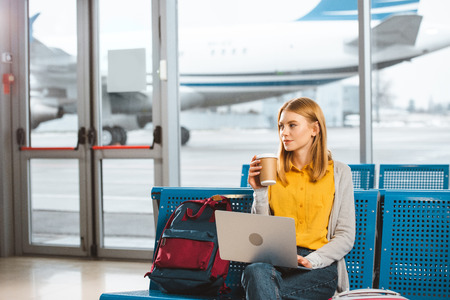 beautiful woman sitting with laptop and holding disposable cup in hand in airport