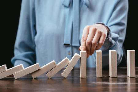partial view of woman sitting at desk and preventing wooden blocks from falling with hand Reklamní fotografie