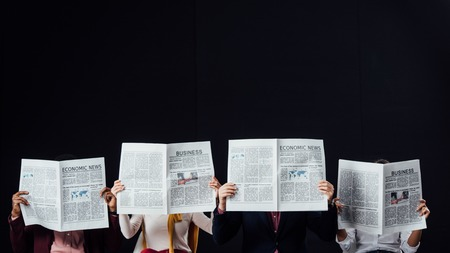group of casual businesspeople with obscure faces reading business newspapers isolated on black Stock fotó