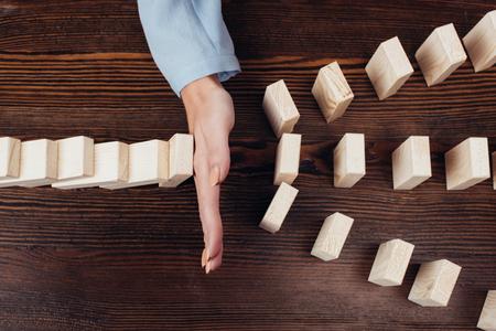 Vista recortada de la mujer evitando que los bloques de madera caigan en el escritorio Foto de archivo