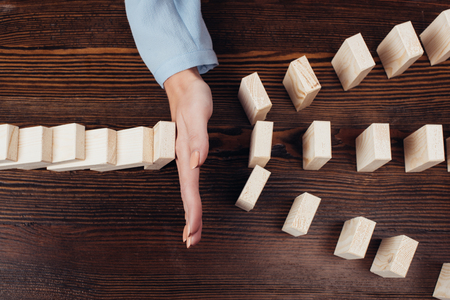 vista ritagliata della donna che impedisce ai blocchi di legno di cadere sulla scrivania Archivio Fotografico