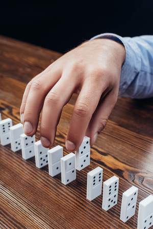 close up view of man picking domino from row on wooden desk Stock Photo