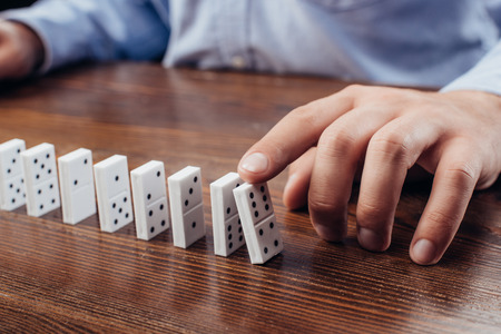 partial view of man pushing domino row on wooden desk