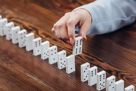 cropped view of woman picking domino from row on wooden desk Stock Photo