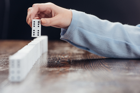 cropped view of woman picking domino from row on wooden desk isolated on black Stock Photo