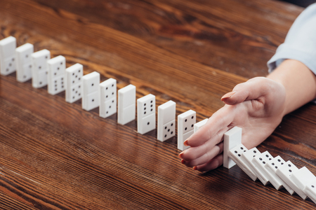 partial view of woman preventing dominoes from falling on wooden desk Stock Photo