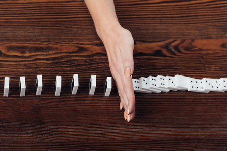 cropped view of woman preventing dominoes from falling on wooden desk Stock Photo