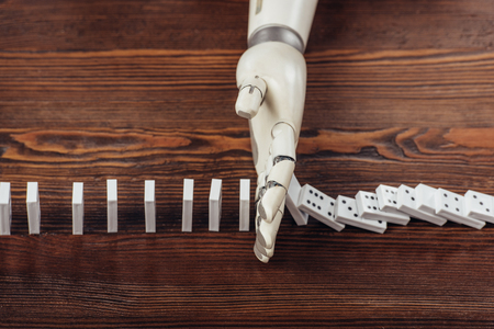 top view of robotic hand preventing dominoes from falling on wooden desk