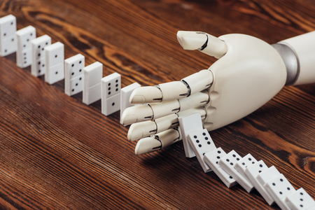selective focus of robotic hand preventing dominoes from falling on wooden desk Stock Photo
