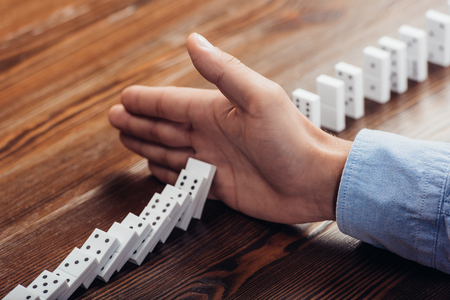 close up view of man preventing dominoes from falling on wooden desk