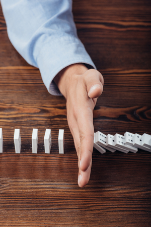 top view of man preventing dominoes from falling on wooden desk Stock Photo