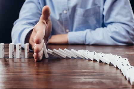partial view of man preventing dominoes from falling on wooden desk Stock Photo