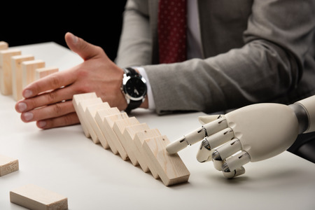 cropped view of robotic hand pushing wooden bricks while man preventing row from falling