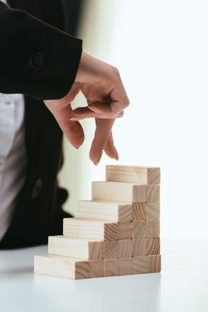 Teilansicht einer Frau, die mit den Fingern auf Holzklötzen geht, die die Karriereleiter symbolisieren