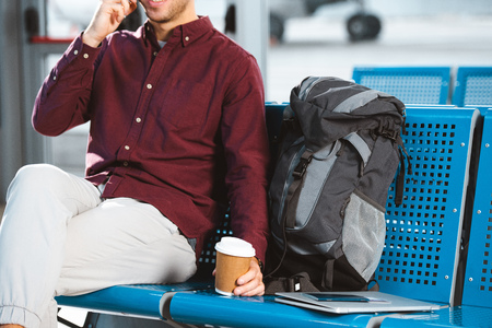 cropped view of man holding paper cup near backpack and laptop Stock Photo