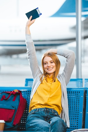 smiling woman holding passport above head in airport near backpack Stock Photo