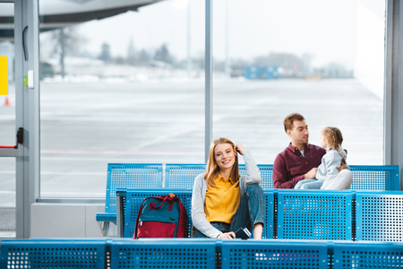 selective focus of smiling woman sitting in airport near backpack with people on background Stok Fotoğraf