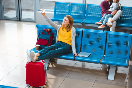 selective focus of smiling woman taking selfie in airport with people on background