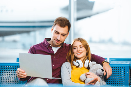 happy boyfriend using laptop near girlfriend with teddy bear in airport Stock Photo