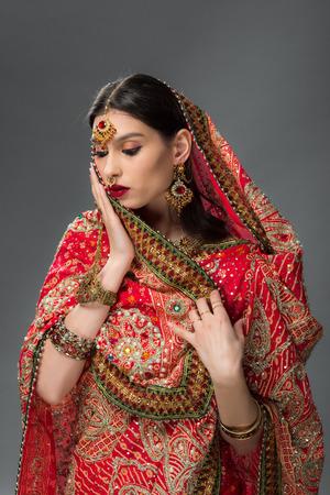 elegant indian woman in traditional sari and bindi, isolated on grey